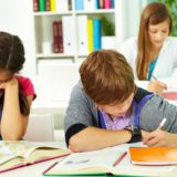 Portrait of smart guy making notes in copybook with his classmates near by